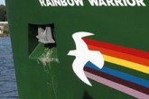 PIcture of the hull of the Rainbow Warrior, with a rainbow and dove painted across its bow.