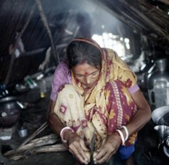 A woman prepares food in a small cabin built on a mud embankment surrounding Padma Pakur island in Bangladesh. When a disaster hits a community, it generally takes women longer to recover from the loss. Photo: Espen Rasmussen/PANOS